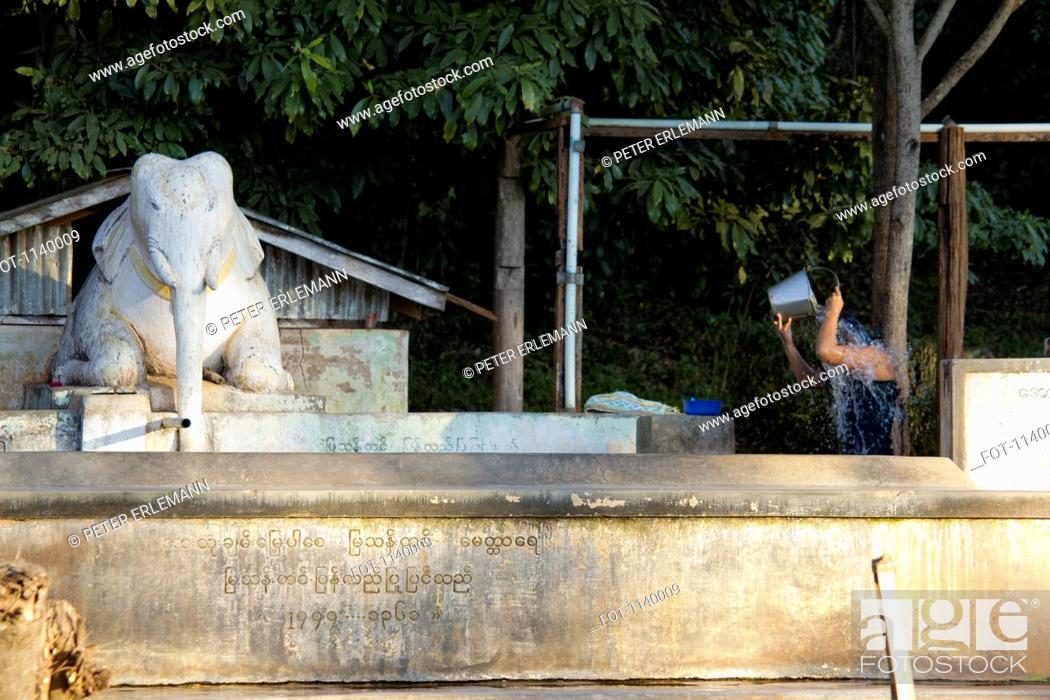 Stock Photo: A person washing hair with a bucket next to an elephant statue, Heho, Burma.