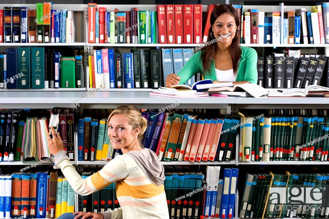 Stock Photo: Young woman studying in library by friend taking book from shelf, smiling, portrait.