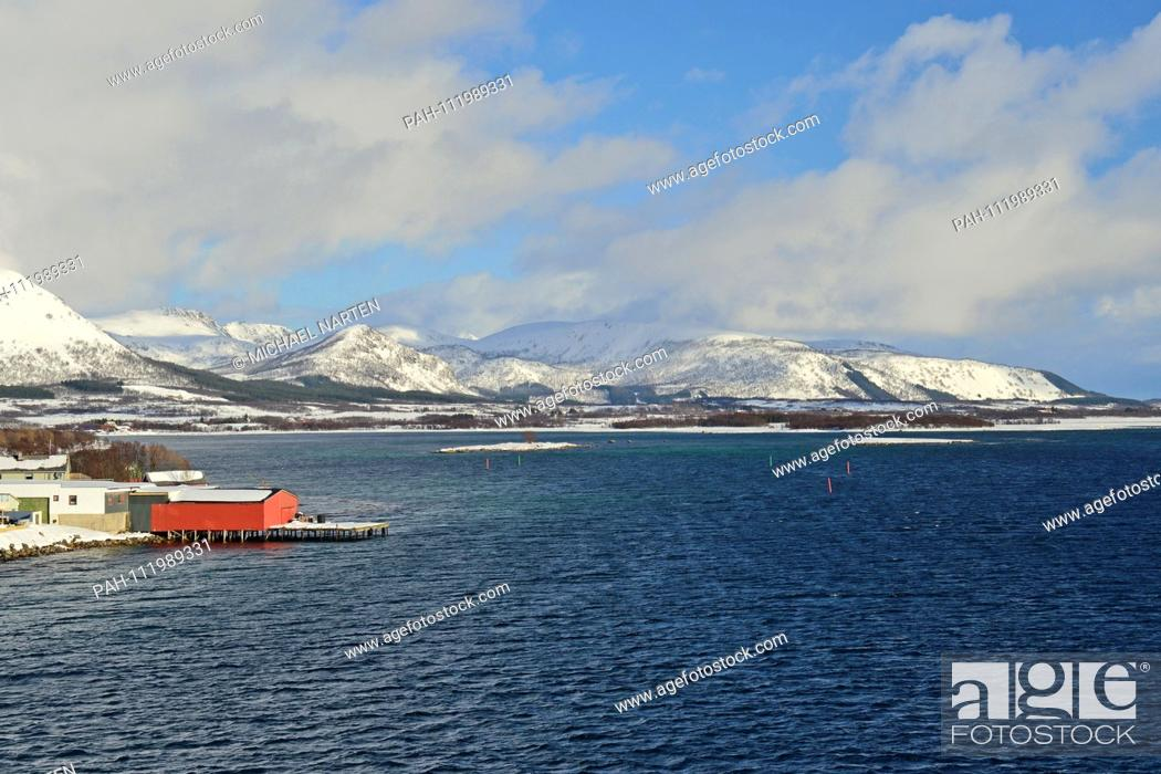 Stock Photo: Red boathouse right on the water's edge of the Vesterålen Island Andøya with the awesome island landscape in the background, 10 March 2017 | usage worldwide.