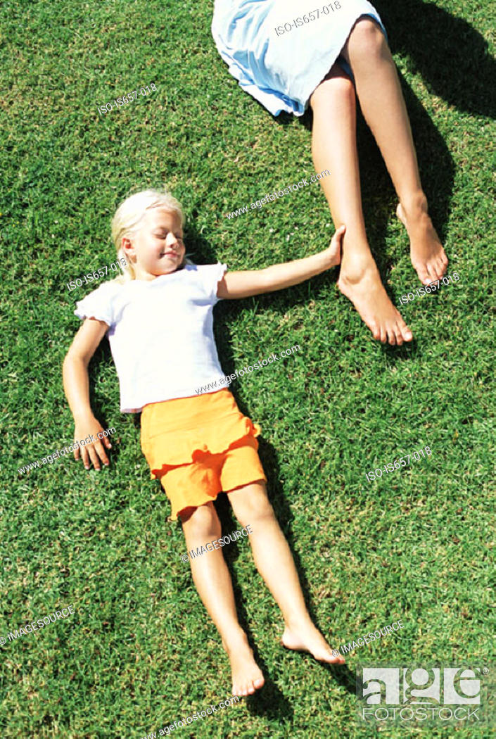 Stock Photo: Mother and daughter lying on lawn.