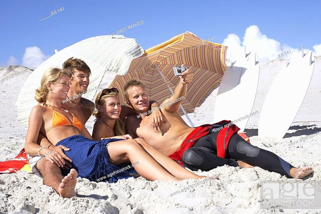 Stock Photo: Four young friends relaxing on sandy beach, man taking photograph with digital camera, smiling.