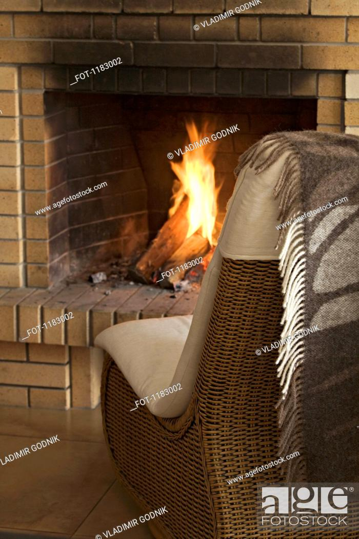 Stock Photo: A wicker chair in front of a roaring fire.