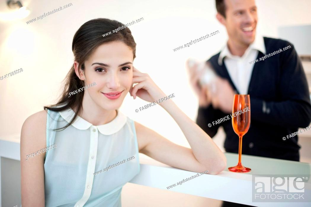 Stock Photo: Woman smiling with her husband shaking cocktail in the background.