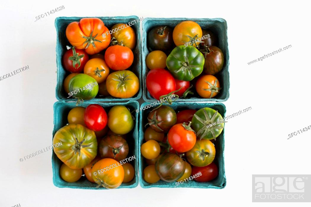 Photo de stock: Heirloom tomatoes in blue cardboard punnets.