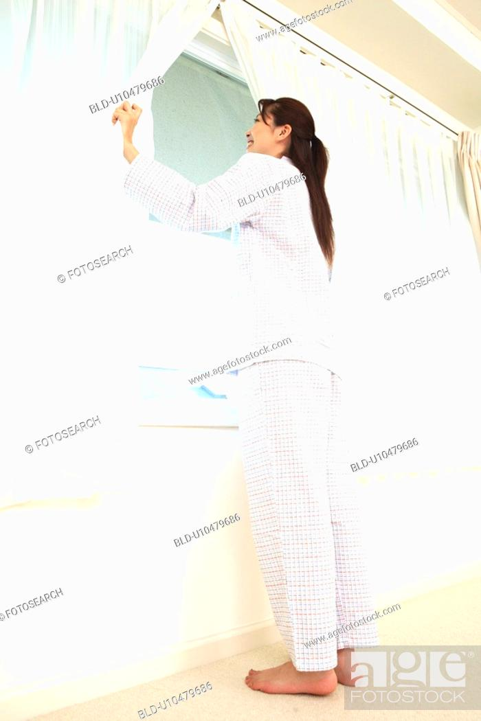 Stock Photo: Woman opening a curtain.