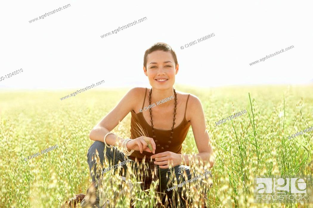 Stock Photo: Young woman crouching in field of grass. portrait.