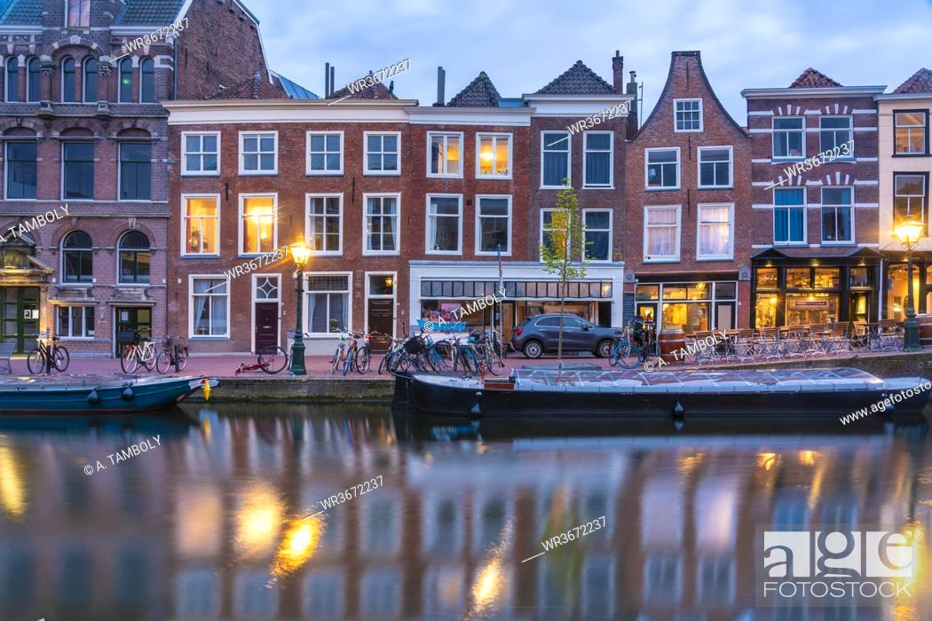 Stock Photo: Netherlands, South Holland, Leiden, Row of historical townhouses along Rhine canal at dusk.