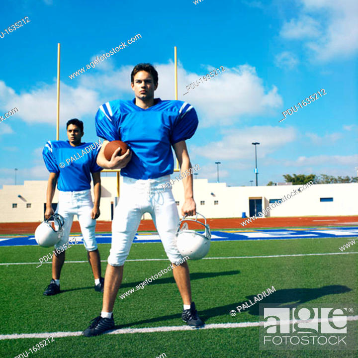 Stock Photo: football players standing in a ground holding helmets.