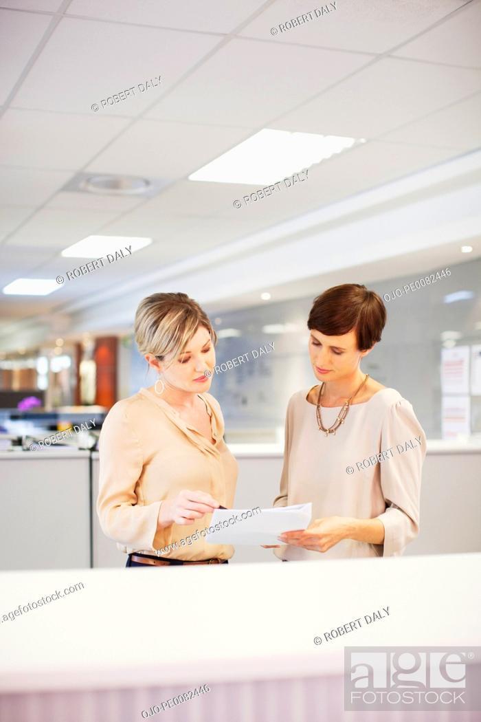 Stock Photo: Businesswomen reviewing paperwork in office.