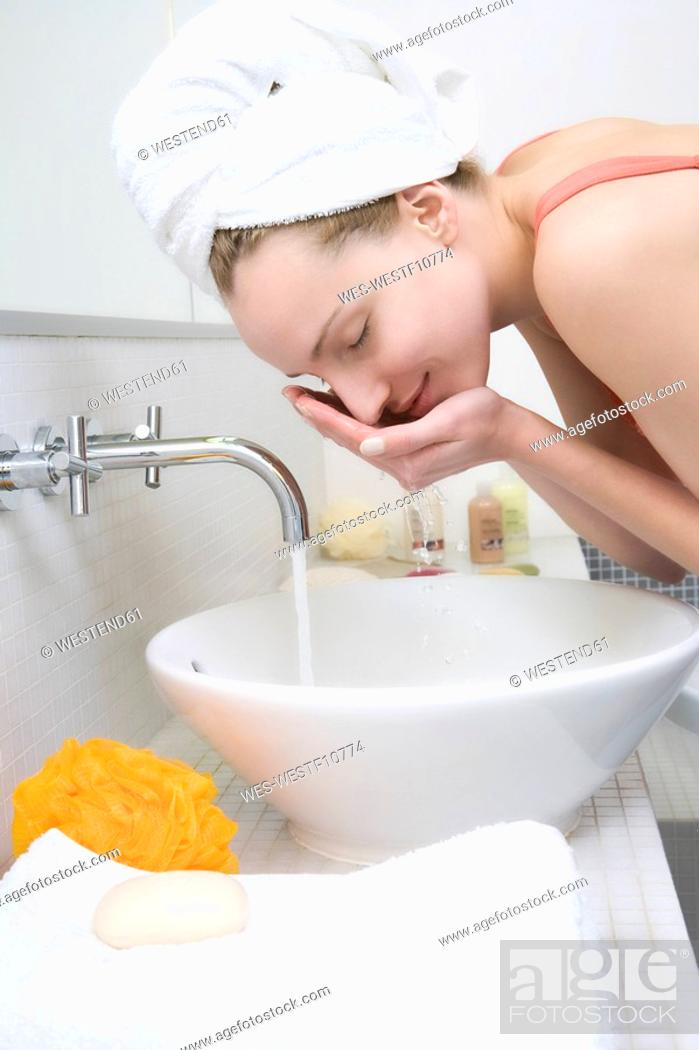 Stock Photo: Young woman washing face, side view.