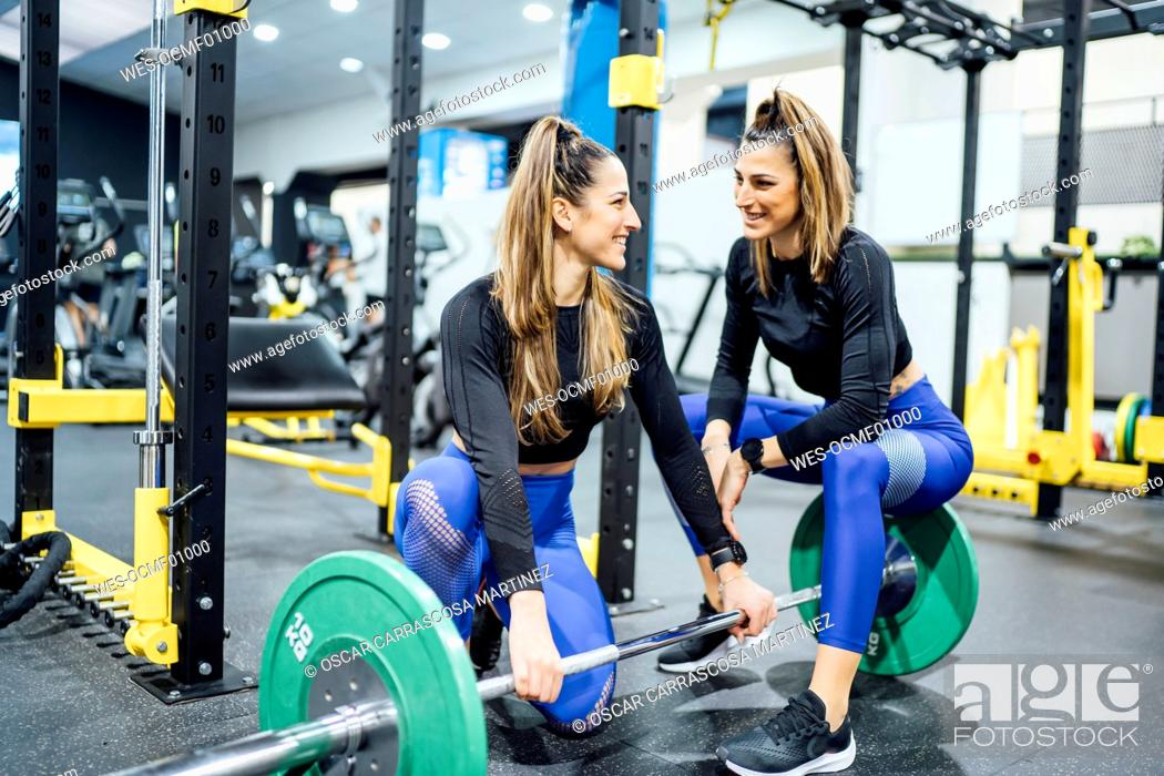 Stock Photo: Smiling twin sisters with barbell in gym.