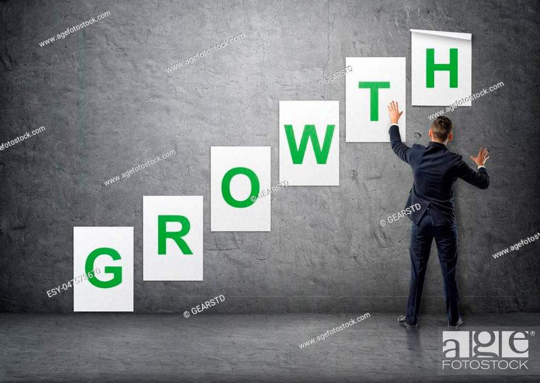 Stock Photo: Businessman putting up posters with letters on a concrete wall that form a 'growth' word. Business staff. Office clothes. Succesful management.