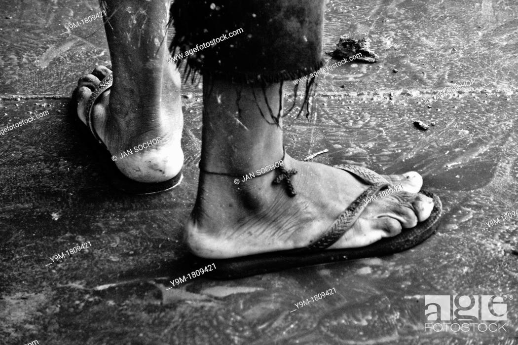Stock Photo: A Brazilian man wears the Christian cross symbol on his ankle as a protection against drowning in the river  Descendants of the Amazonian indigenous people are.