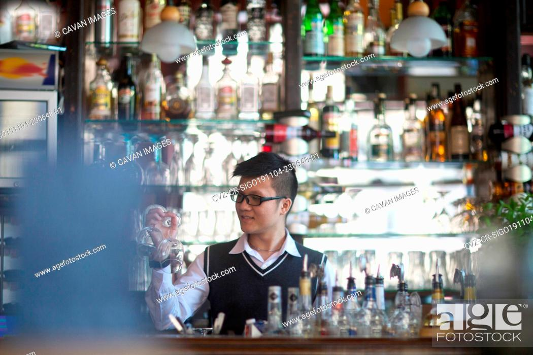 Stock Photo: young asia waiter in a bar.