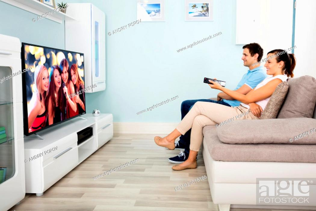 Stock Photo: Young Couple Sitting On Sofa In Front Of Television Watching Movie At Home.