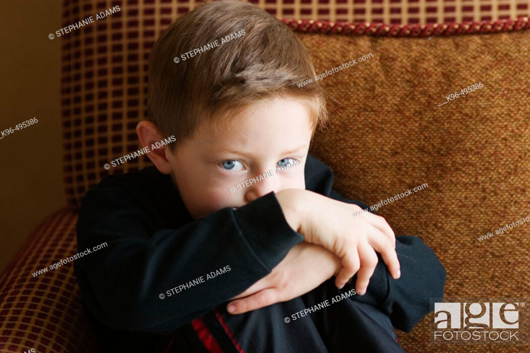 Stock Photo: young boy on cushion chair.