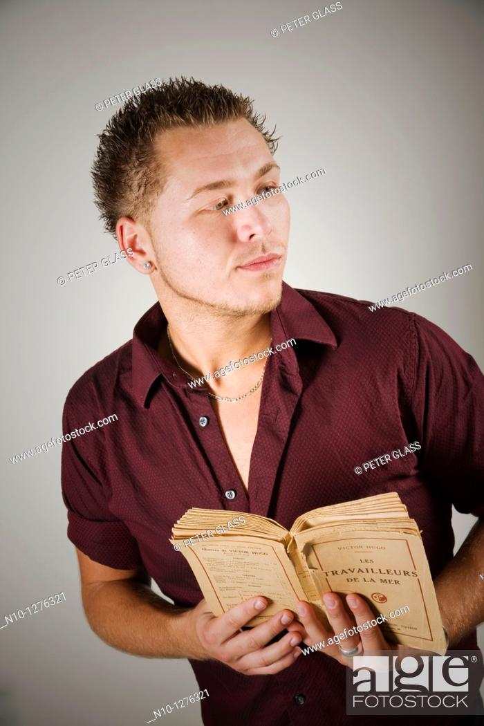 Stock Photo: Young man holding a French book.