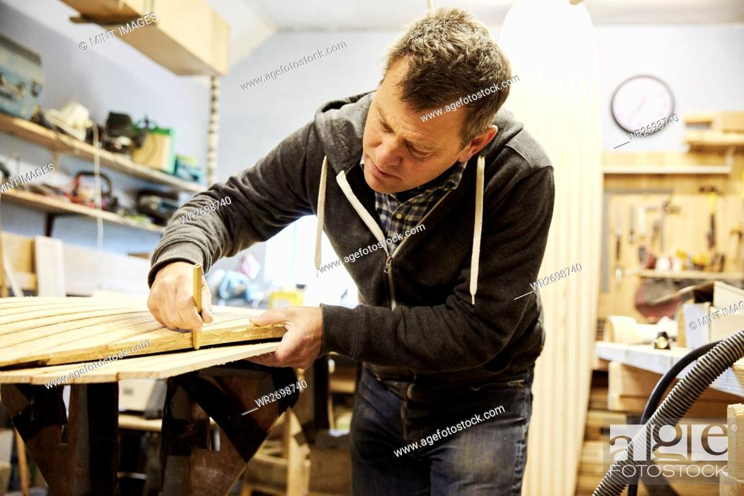 Photo de stock: Man working on the edge of a wooden shaped board in a woodwork shop.