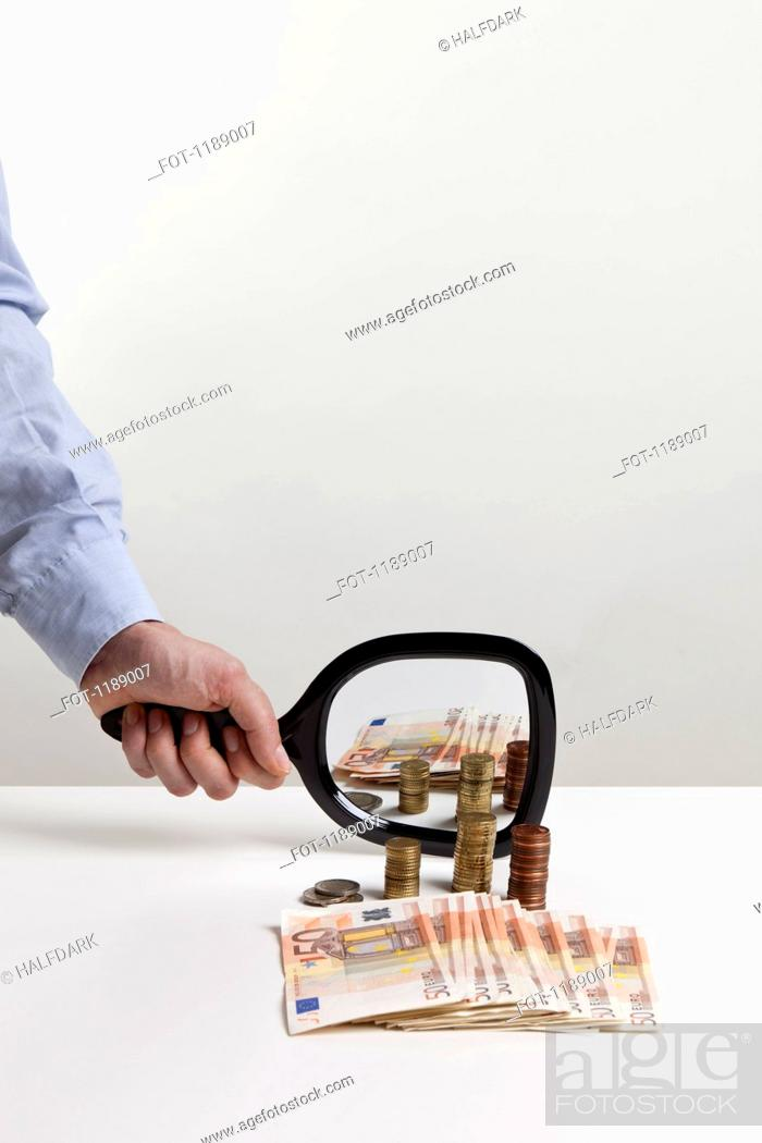 Stock Photo: A man holding a hand mirror up to a pile of European Union currency.
