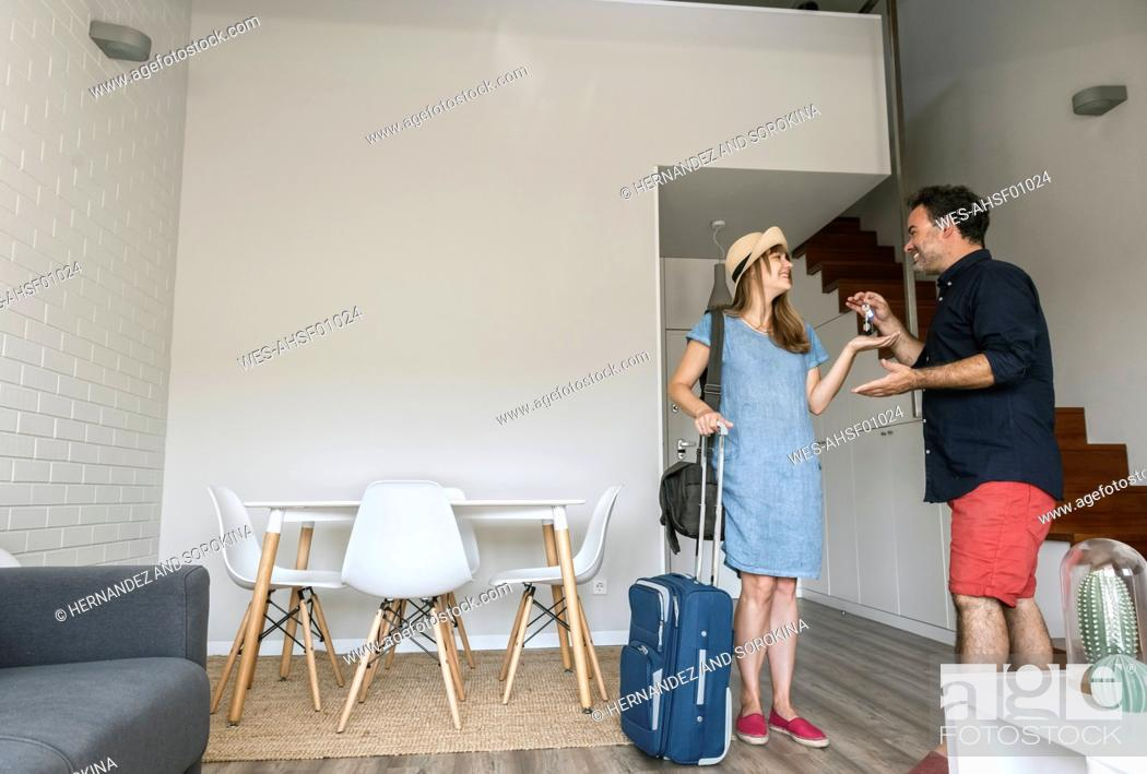 Stock Photo: Tourist gettting the key of modern vacation home from owner.