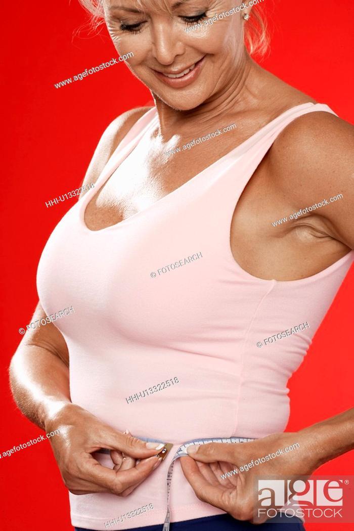 Stock Photo: Mature woman measuring waist.