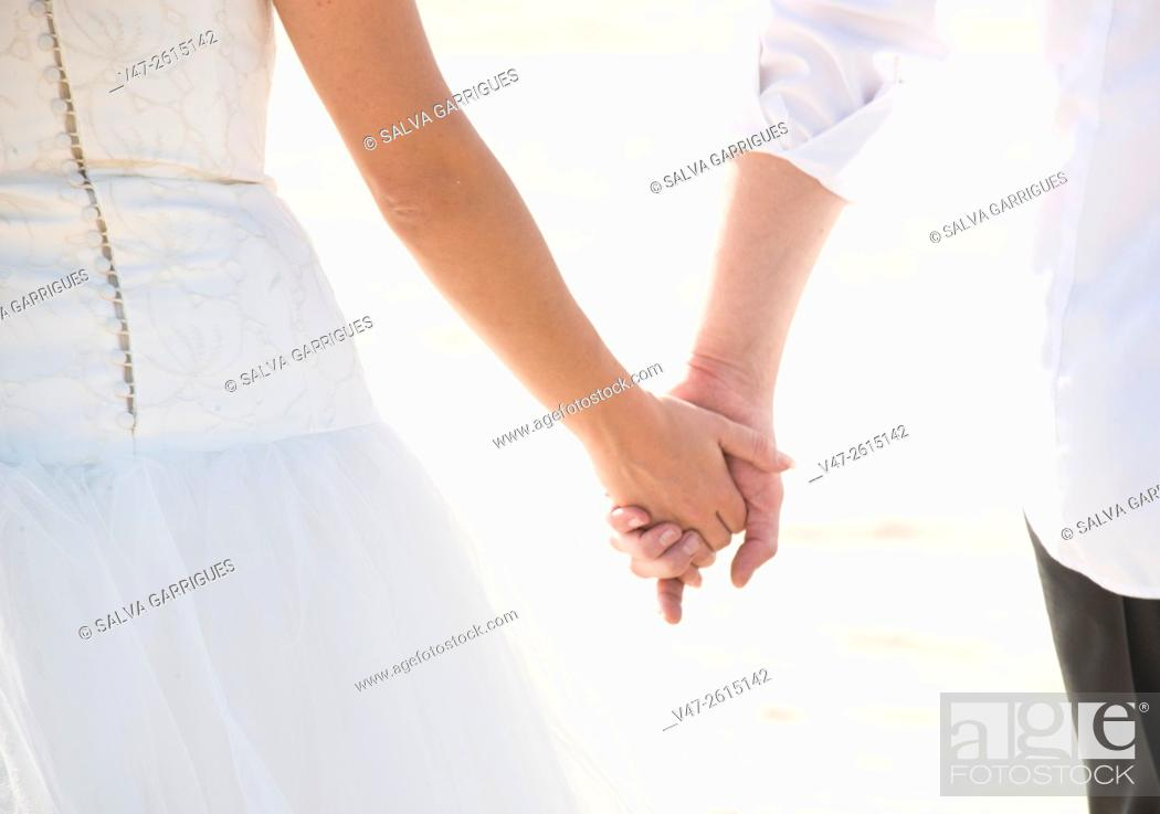 Imagen: Wedding couple holding hands on their wedding day.