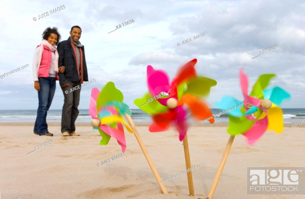 Stock Photo: Pinwheels on beach, couple in background blurred motion.
