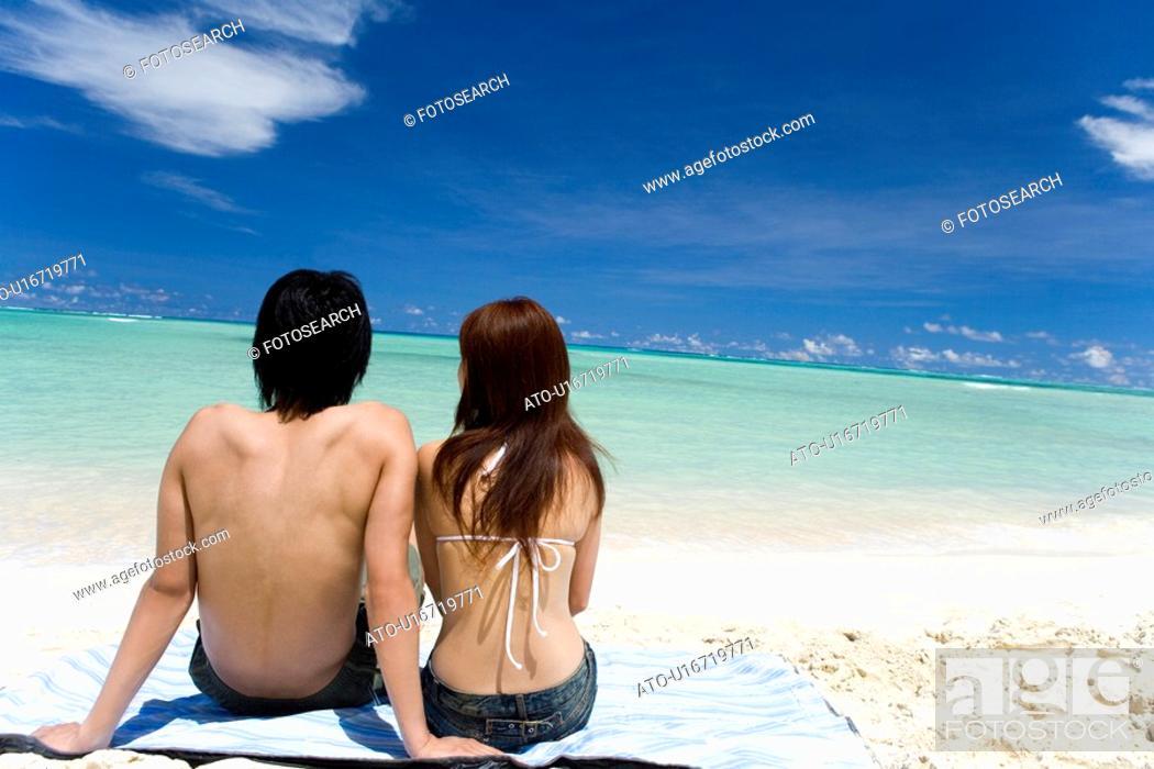 Imagen: Young couple sitting on beach, Saipan, USA.