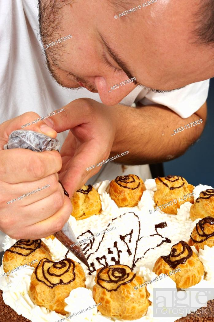 Stock Photo: A pastry chef decorating a cake with whipped cream.