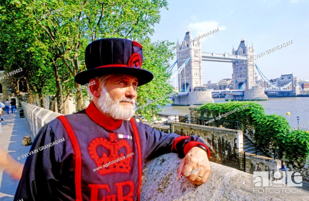 Stock Photo: LOndon tower beefeater in front of the tower bridge  London  England.