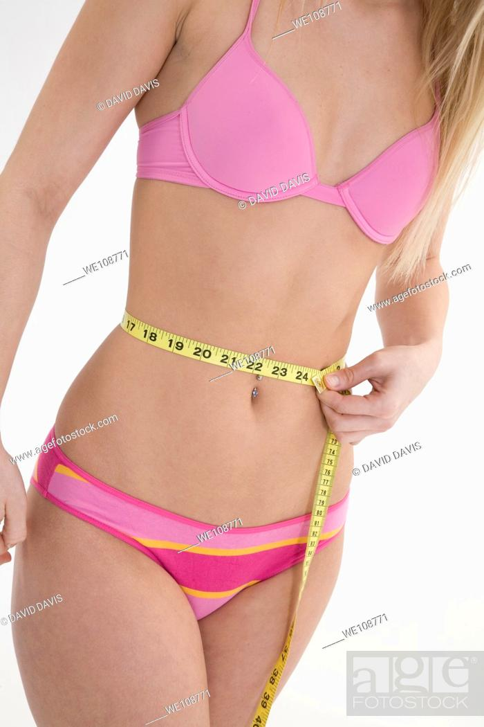 Stock Photo: Young woman in underwear measuring her waist.