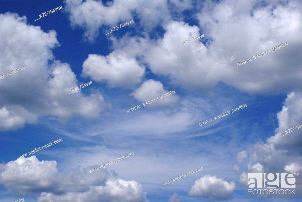 Stock Photo: On this beautiful summer day white puffy clouds float around in a deep blue sky.