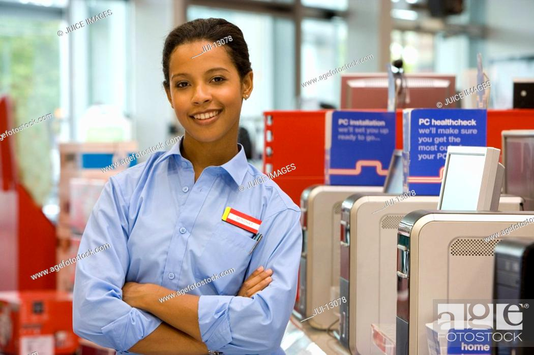 Stock Photo: Computer saleswoman in shop with arms crossed, smiling, portrait.