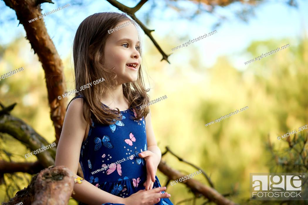 Photo de stock: two adorable girls in summer dresses are climbing a tree in the forest.