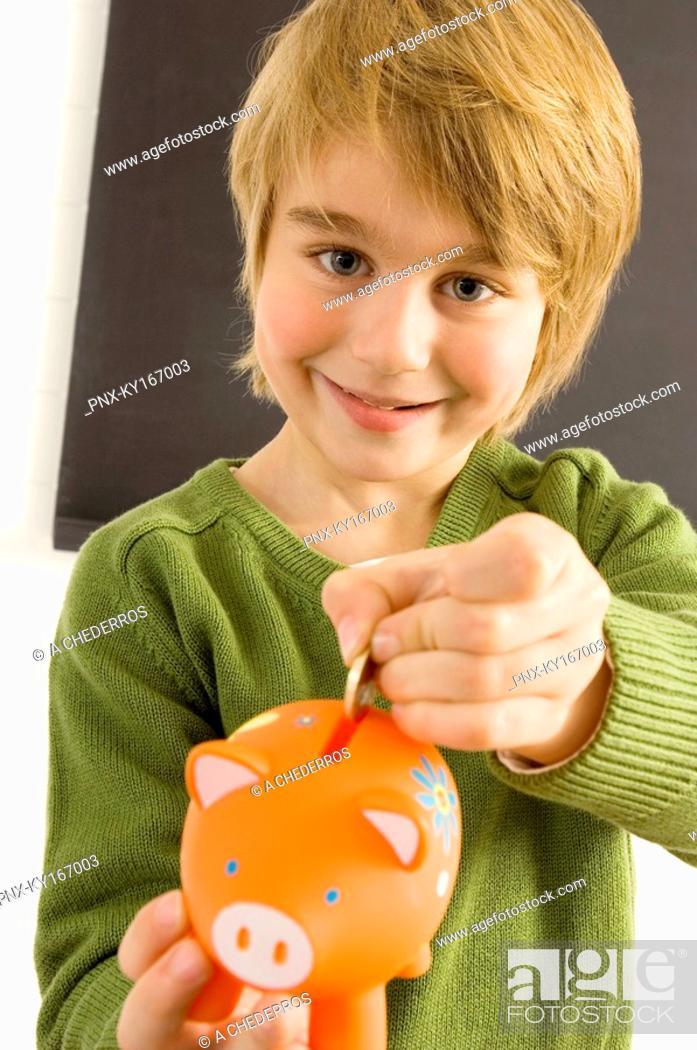 Stock Photo: Boy putting a coin into a piggy bank.