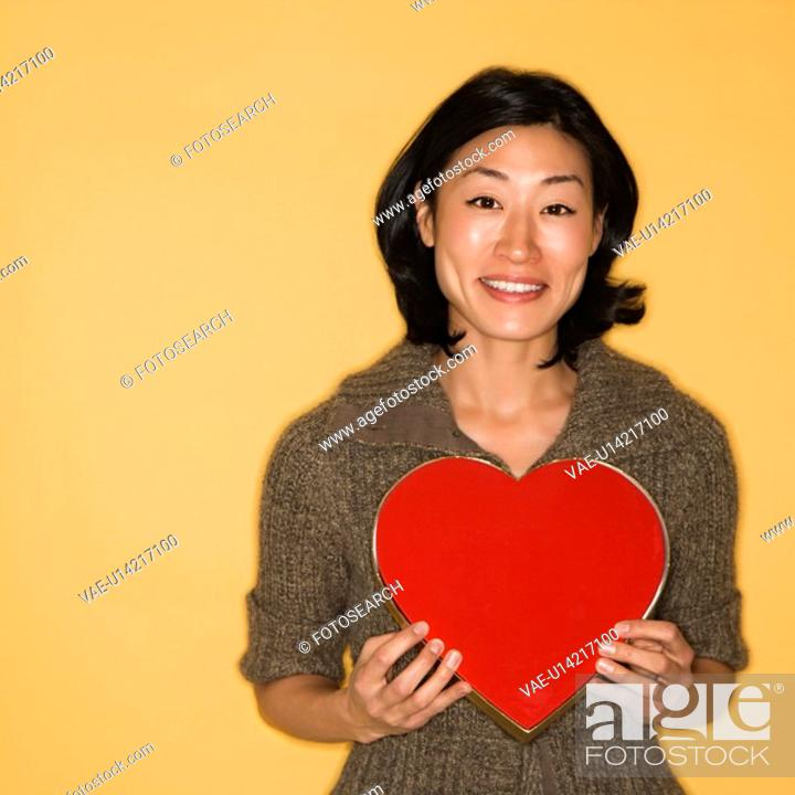 Stock Photo: Pretty mid adult Asian woman holding red heart shaped box.