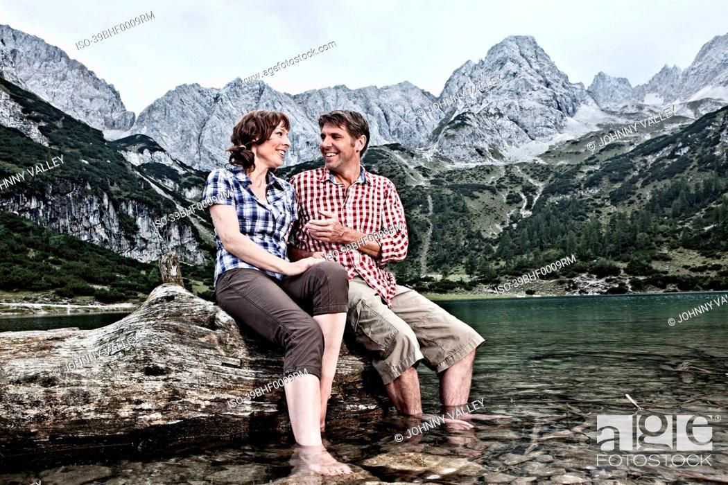 Imagen: Smiling couple dangling feet in lake.