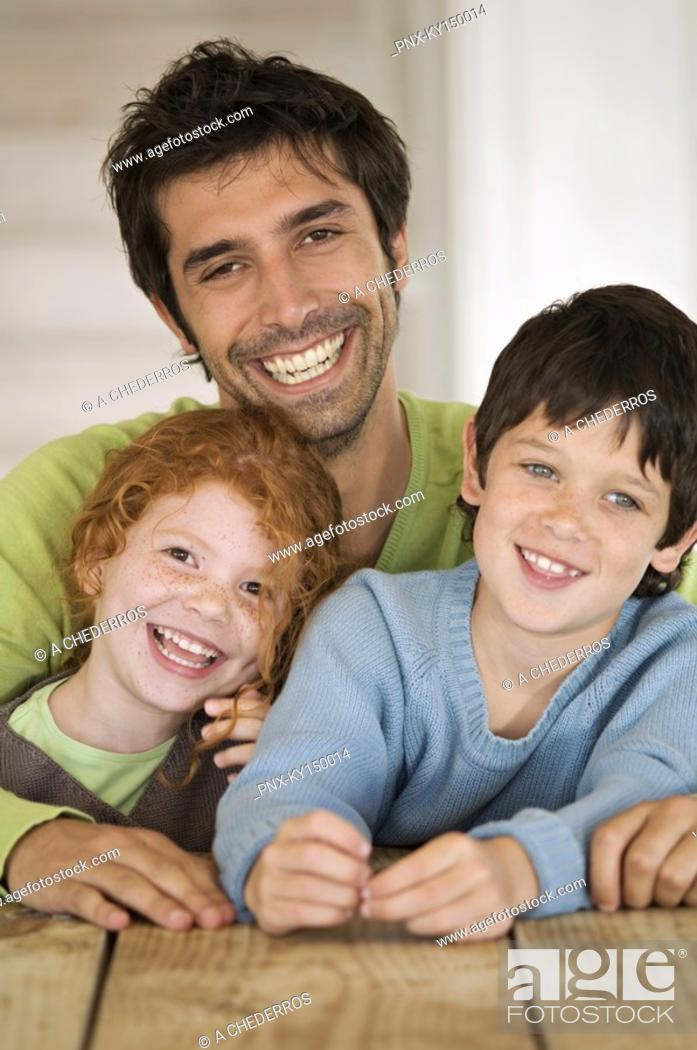 Stock Photo: Father and 2 children smiling for the camera.