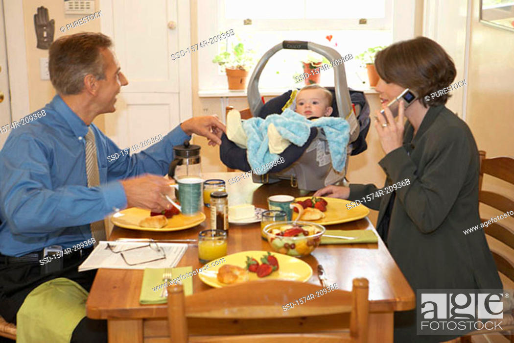 Stock Photo: Side profile of a mid adult couple with their son at a dining table.
