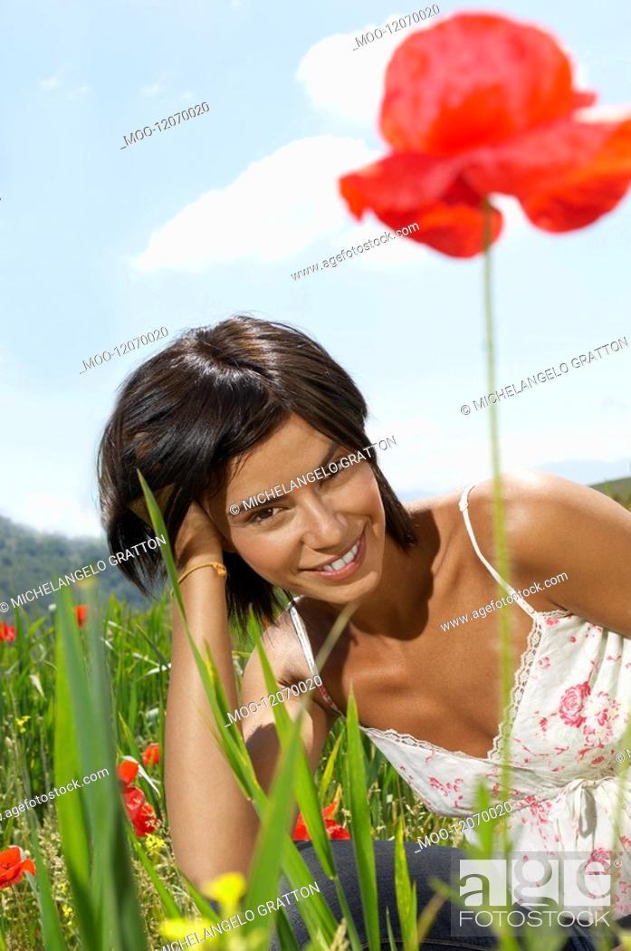Stock Photo: Woman Lying in flowery Meadow portrait.