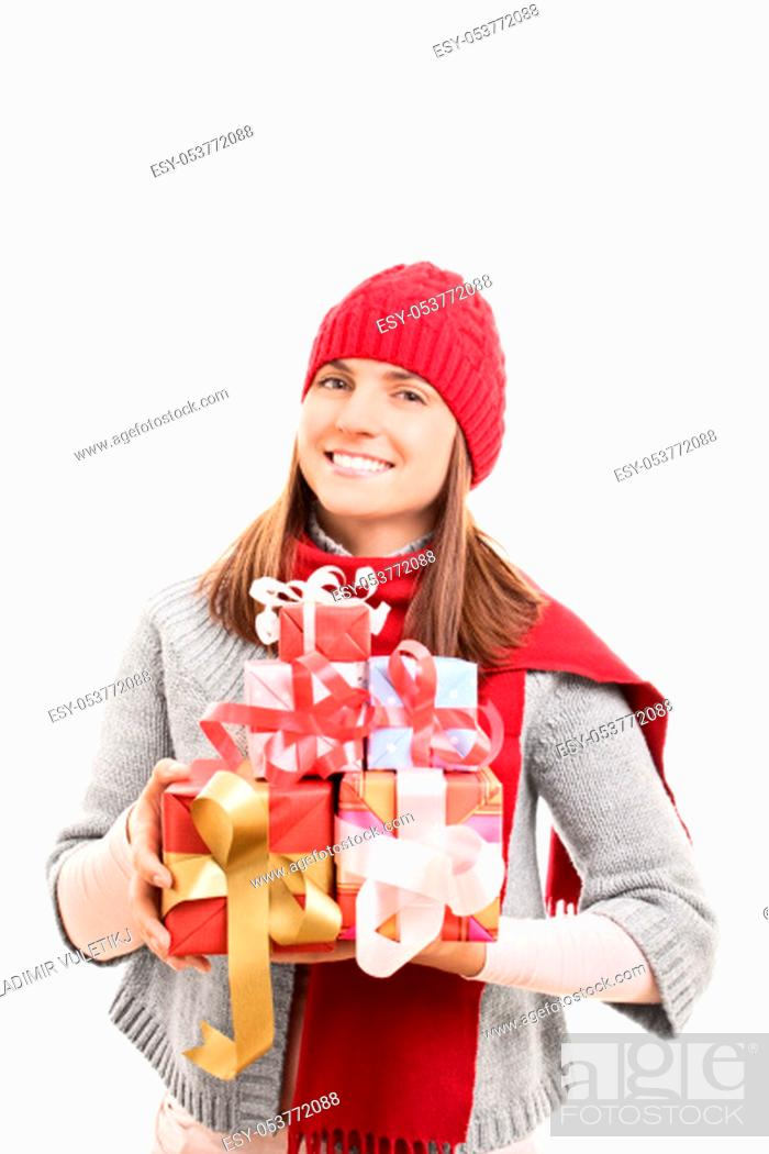Stock Photo: My Christmas shopping is done. Beautiful young woman in winter clothes holding wrapped presents, isolated on white background.