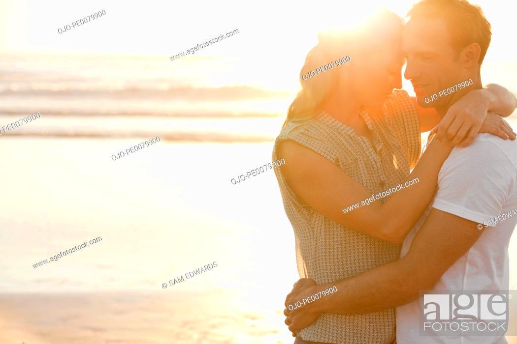 Stock Photo: Serene couple hugging on beach at sunset.