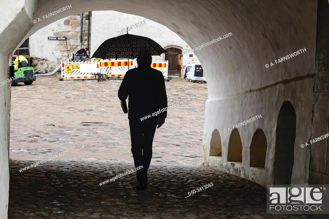 Stock Photo: Turku, Finland A man with umbrella enters the main vaulted gate at the 13th century medieval Turku Castle.