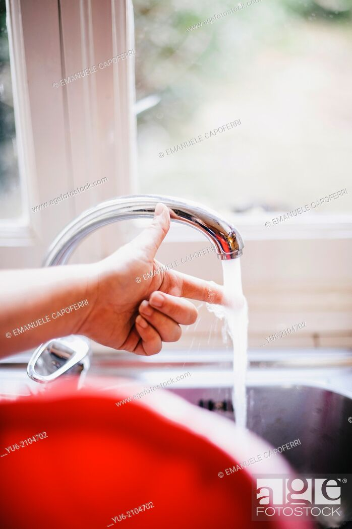 Stock Photo: Water flows from the tap in the kitchen and a finger if it feels hot.