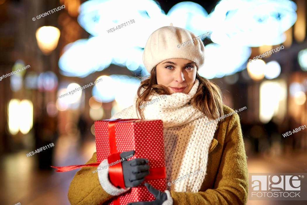 Stock Photo: Portrait of smiling woman with Christmas present in the evening.