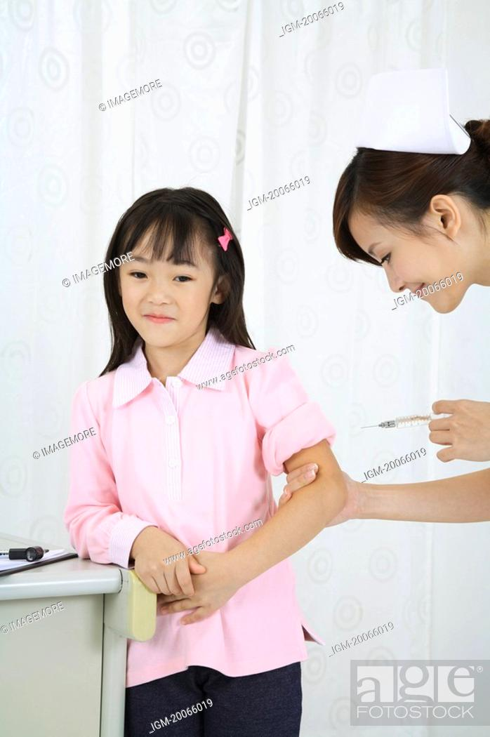 Stock Photo: Young nurse taking injection for little girl.