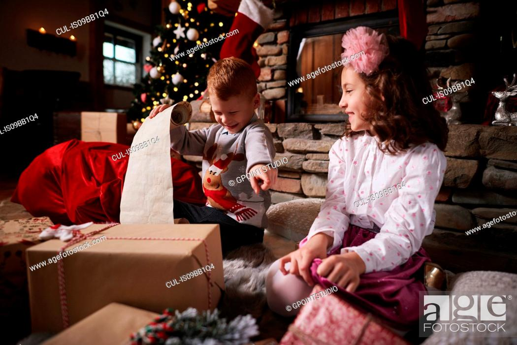 Imagen: Young girl and boy sorting Christmas gifts, young boy rolling list.