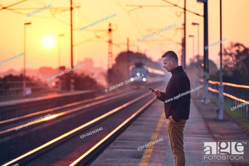 Stock Photo: Young man waiting at railroad station platform and using smart phone against commuting train at sunrise.