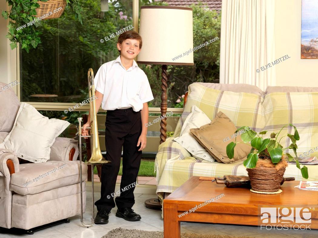 Stock Photo: Portrait of boy holding trombone in sitting room.