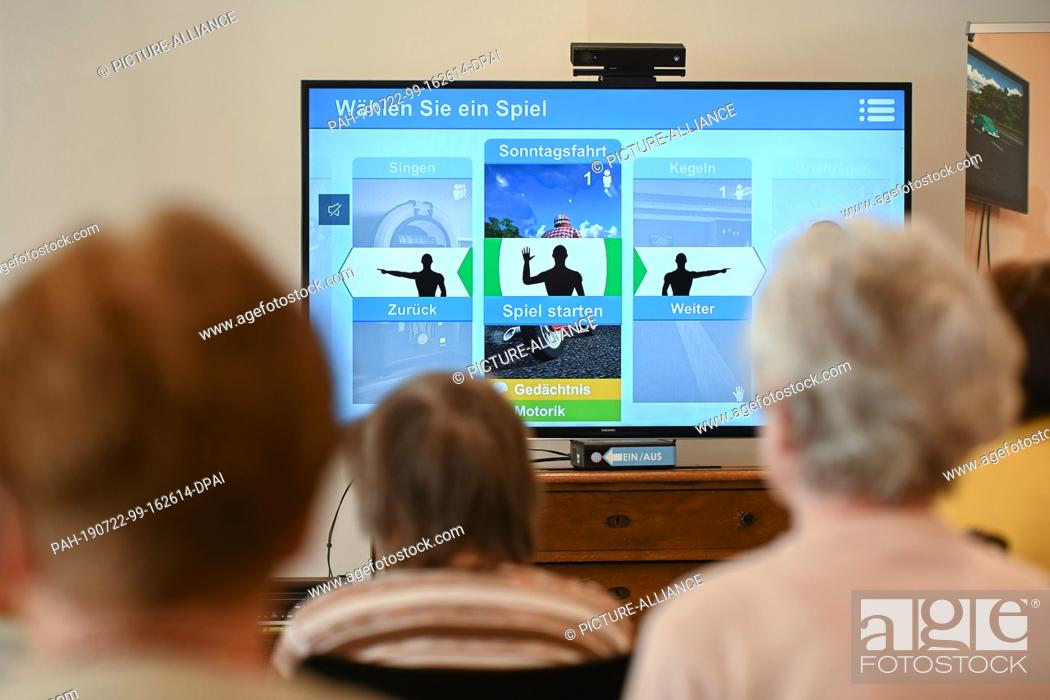 Stock Photo: 22 July 2019, Hessen, Bad Arolsen: Residents of the Helenenheim Bad Arolsen are sitting in front of the digital game console.